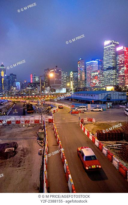 two taxis drive along temporary construction site roadway with Hong Kong skyline in the background