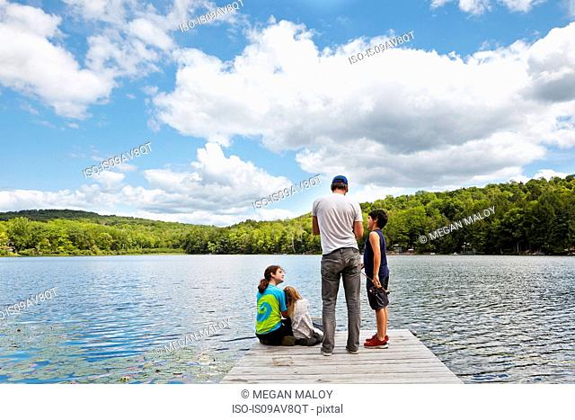 Father and children on pier by lake, New Milford, Pennsylvania, US
