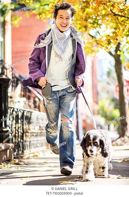 Teenage boy(16-17) walking with dog