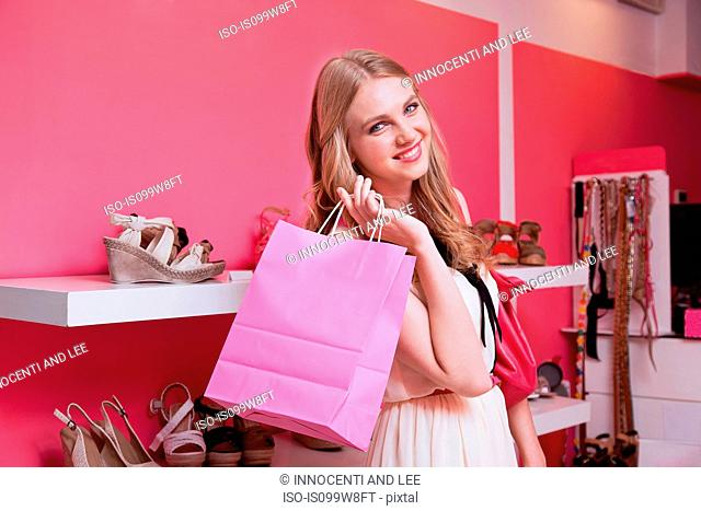 Young woman in shoe store with pink shopping bag