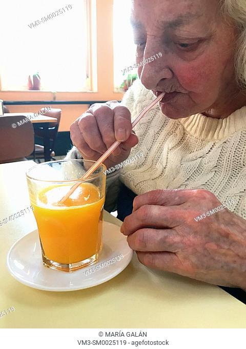 Elderly woman drinking orange juice using a straw
