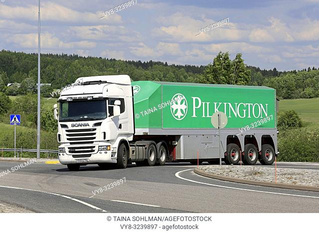 White Scania R560 truck and Pilkinton glass transport trailer on road intersection on a day of summer in Salo, Finland - June 2, 2018