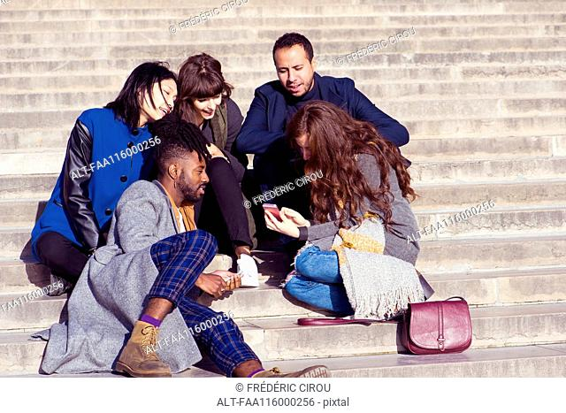 Friends sitting on steps and using smartphone