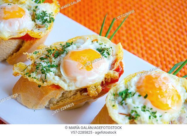 Spanish tapa: quail eggs and tomato sauce on toast. Close view