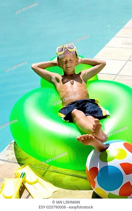 Boy (9-11) on inflatable chair by swimming pool, arms behind head, elevated view