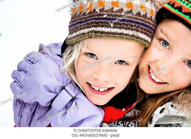 Smiling girls hugging in snow