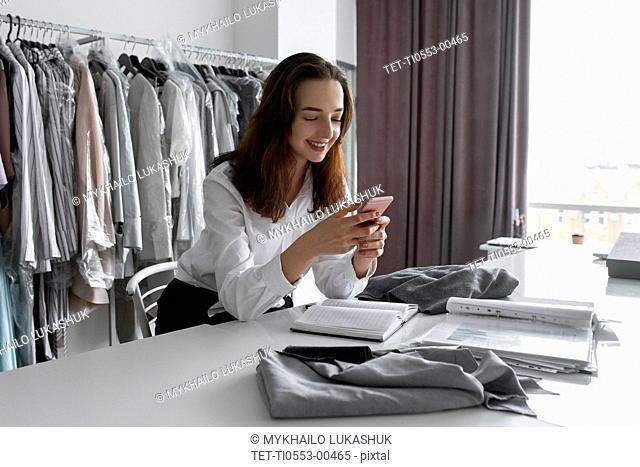 Fashion designer using smartphone in studio