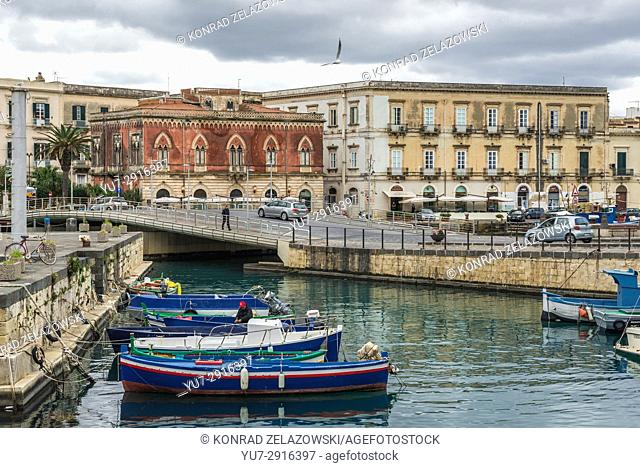 Local fisherman's boats at the marina in Syracuse city, southeast corner of the island of Sicily, Italy. Santa Lucia bridge on background