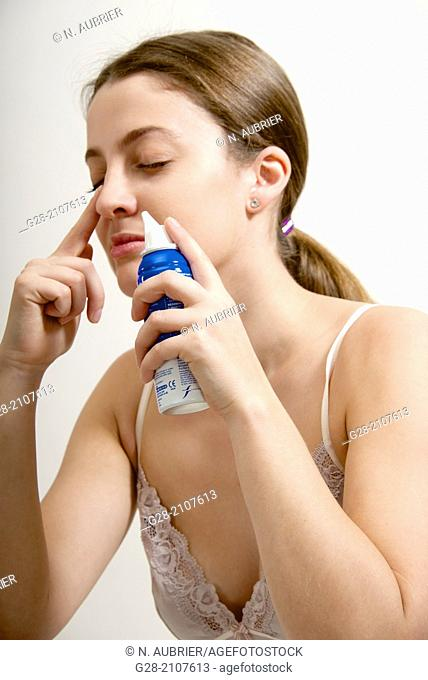 Young beautiful woman in pink underwear, cleaning one nostril of her nose with sea water spray