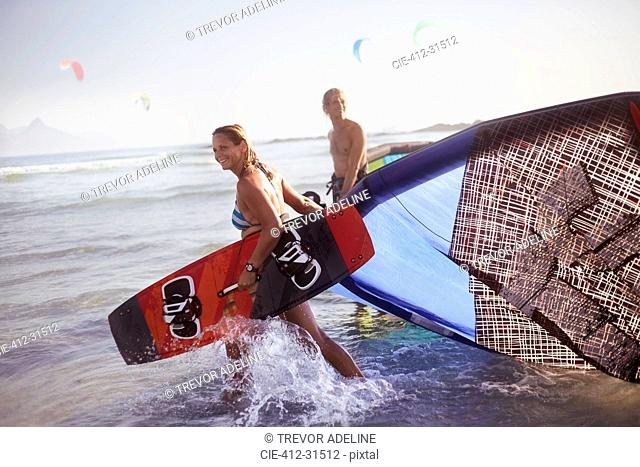 Couple pulling kiteboarding equipment into ocean surf