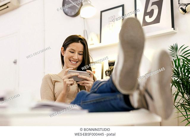 Young female entrepreneur having a rest using her smartphone at home office