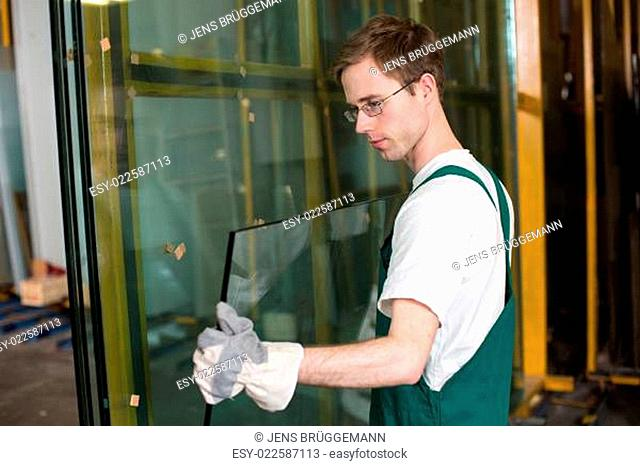 Glazier in workshop handling glass