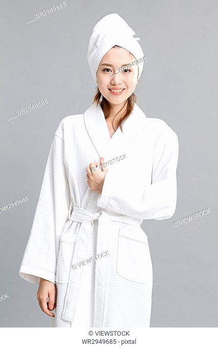 A young woman wearing a bathrobe