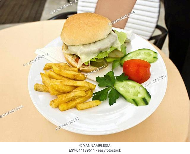 Man holds plate with cheeseburger with French fries, sliced cucumbers and tomatoes