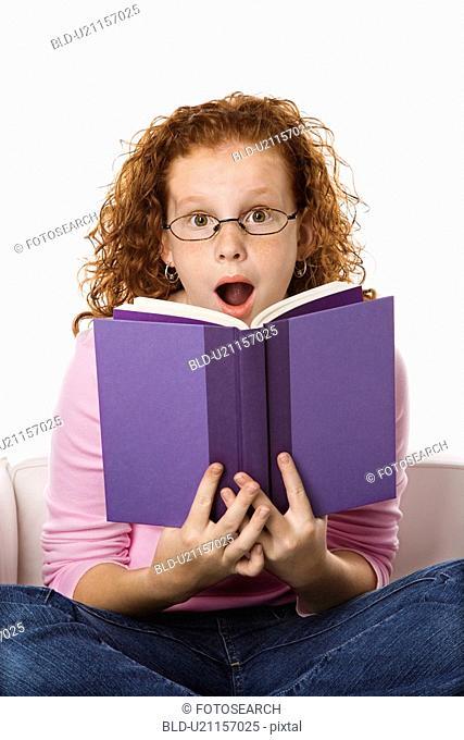 Caucasian female child sitting reading book looking surprised