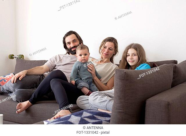 Portrait of family with two children sitting on sofa in living room