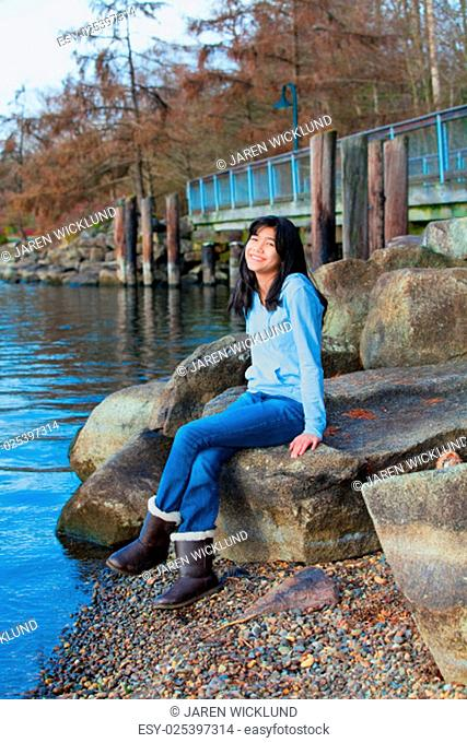 Young biracial teen girl in blue shirt and jeans sitting on large boulder or rocks along rocky lake shore, smiling and reclining