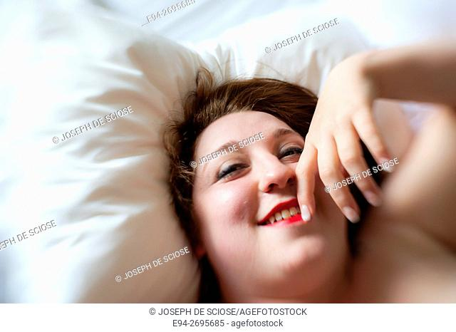 Portrait of a partially nude 24 year old woman lying on a bed and smiling at the camera