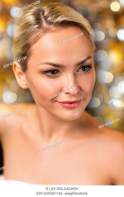 people, beauty, spa, healthy lifestyle and relaxation concept - close up of beautiful young woman sitting in bath towel over holidays lights background