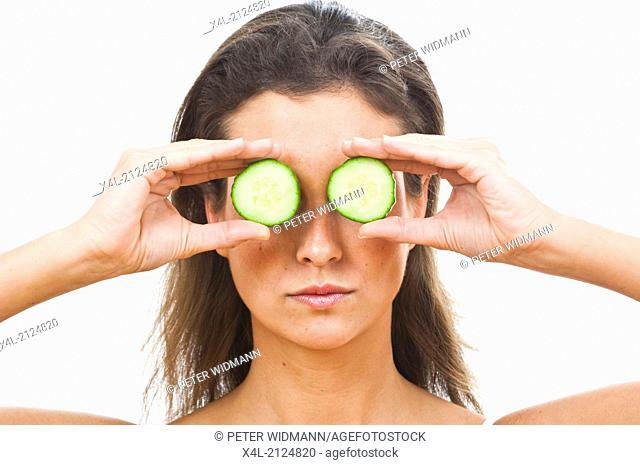 Young woman holding two slices of cucumber in front of her eyes (model-released)