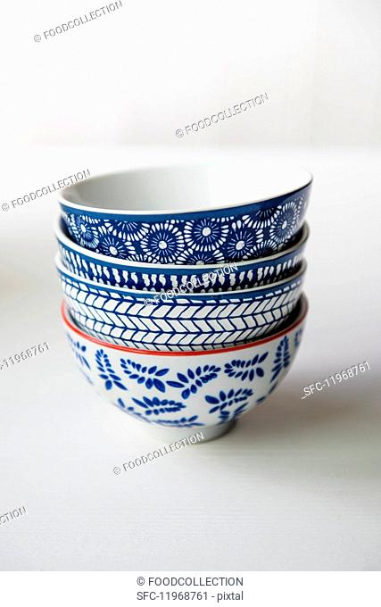 Four blue and white patterned bowls on a white surface