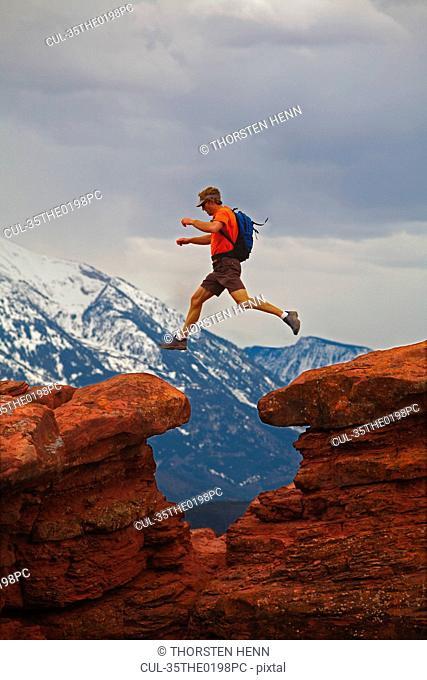 Hiker jumping between rocks