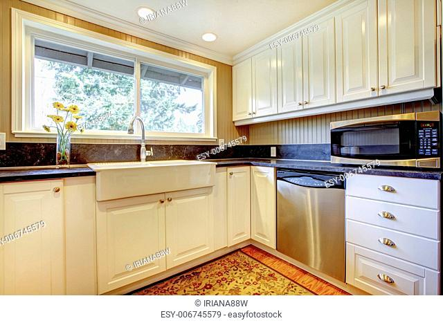 White kitchen interior with large sink and window
