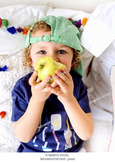 Portrait of little boy sitting on the couch eating an apple