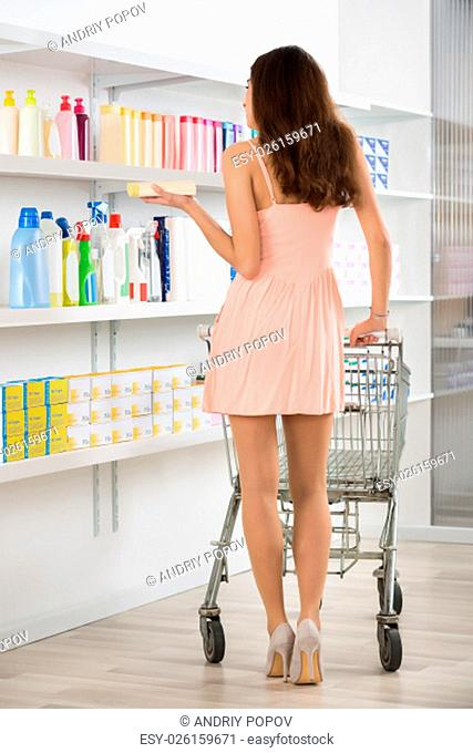 Full length rear view of woman with shopping cart buying beauty products in supermarket