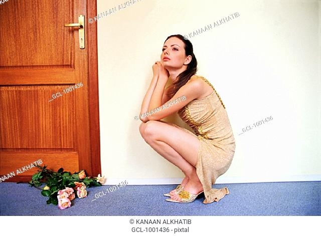 Woman cowering in front of a bunch of roses