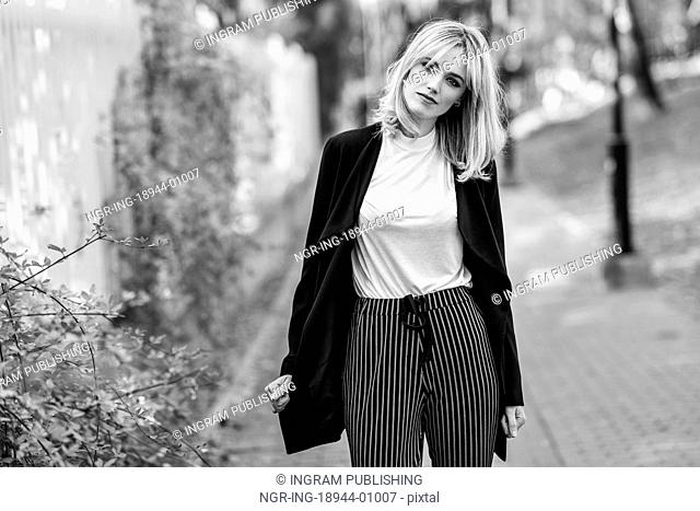 Beautiful blonde woman in urban background. Young girl wearing black blazer jacket and striped trousers standing in the street