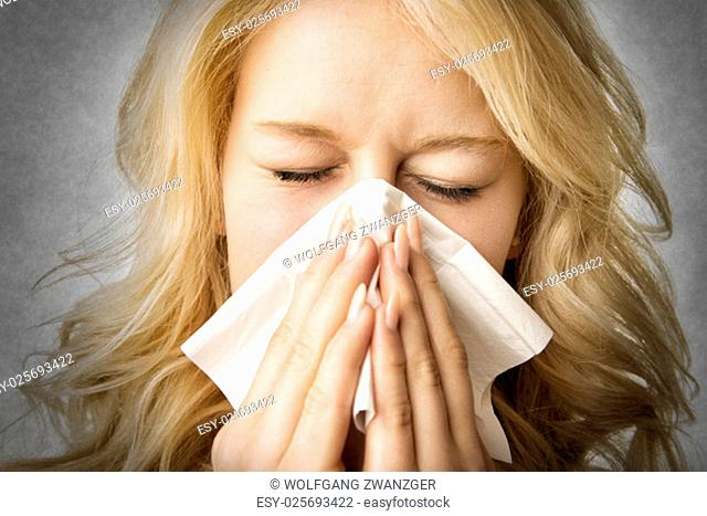 Portrait of a ill blond woman who is sneezing in a tissue