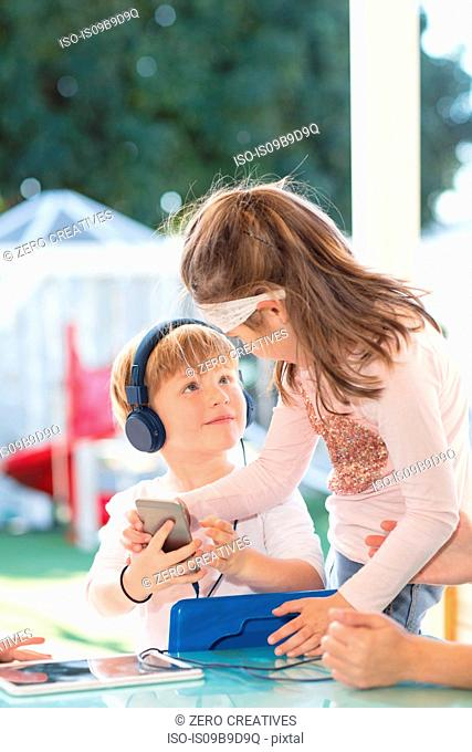 Two young children holding smartphone, young boy wearing headphones