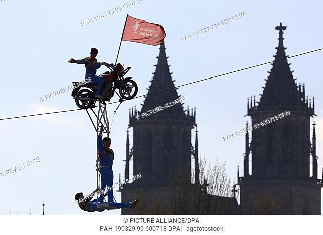 "29 March 2019, Saxony-Anhalt, Magdeburg: High wire artists of the """"Geschwister Weisheit"""" ride a motorbike over a wire rope stretched in front of the cathedral..."