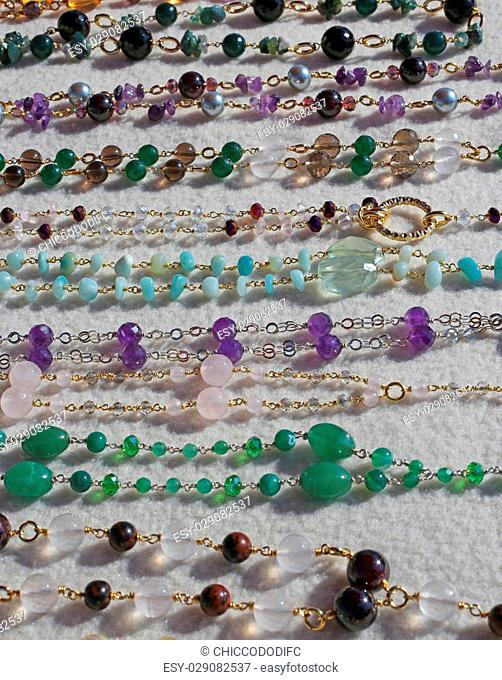 many valuable necklaces in gold and gemstones for sale at flea market
