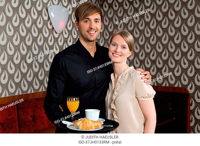Waiter with tray of food hugging woman