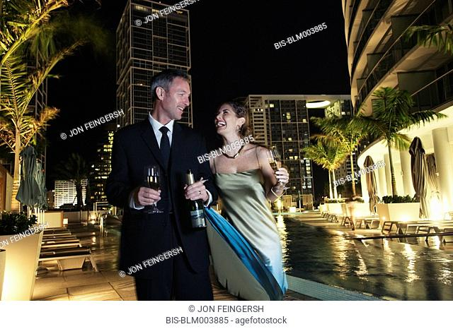 Couple poolside with champagne bottle and glasses