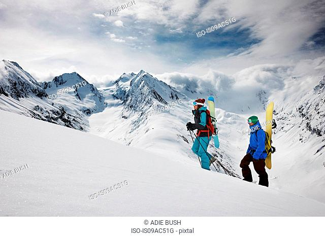Young people climbing to top of mountain carrying ski equipment