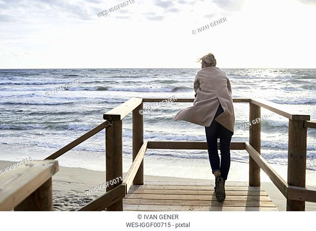 Spain, Menorca, back view of senior woman standing on boardwalk in winter looking at the sea