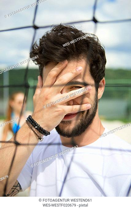 Young man covering his face at net of beach volleyball field