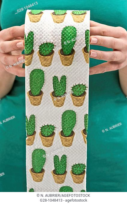 woman's hands holding a roll of toilet paper printed with green cactuses to express toilet difficulties