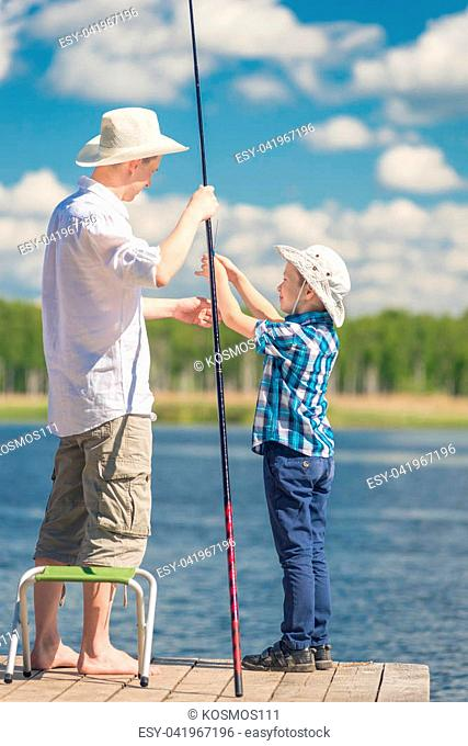 son helps his father to fish in the lake