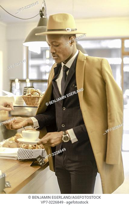Man in bakery with coffee, Munich, Germany