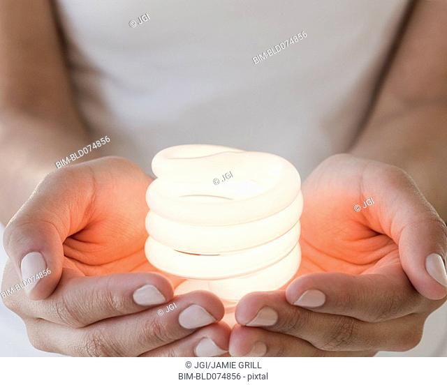 Woman holding glowing compact fluorescent bulb