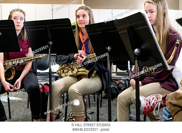 Caucasian students holding saxophones in music class