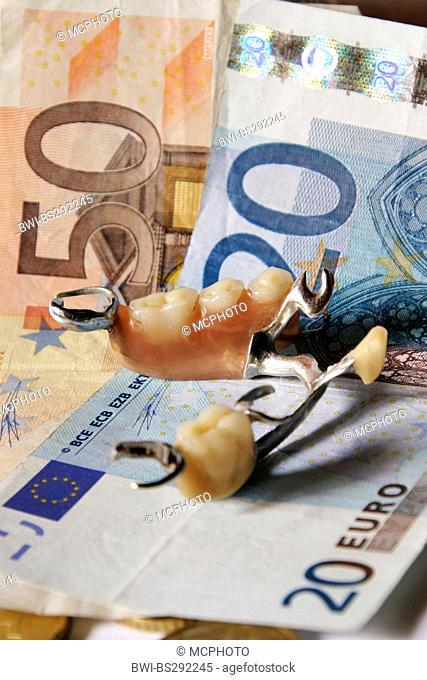 artificial dentures lying on Euro bills