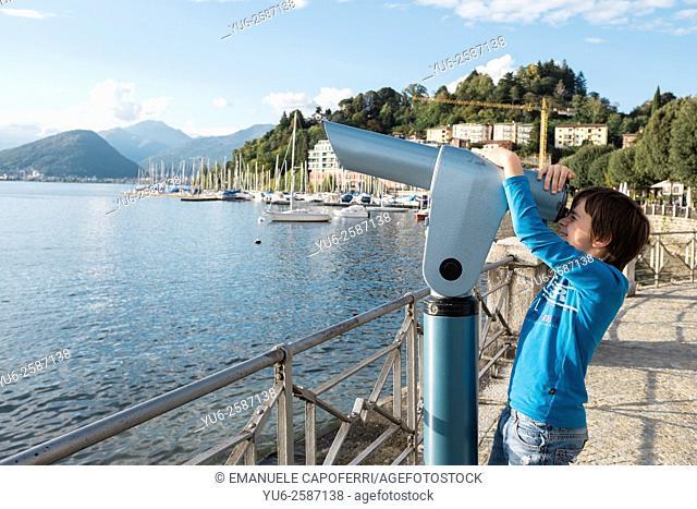 Child looks view through the telescope for tourists, Laveno, Italy