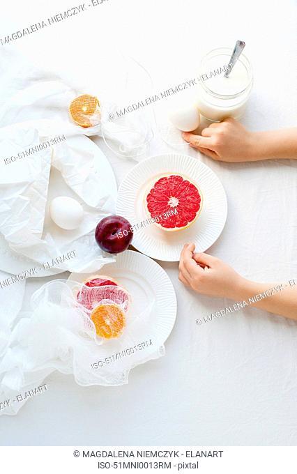 Hands arranging plates of fruit