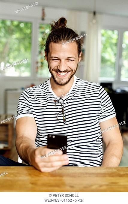 Young man with a bun sitting at home, using smartphone