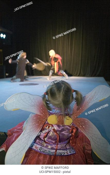 Young girl watching boys performing on stage